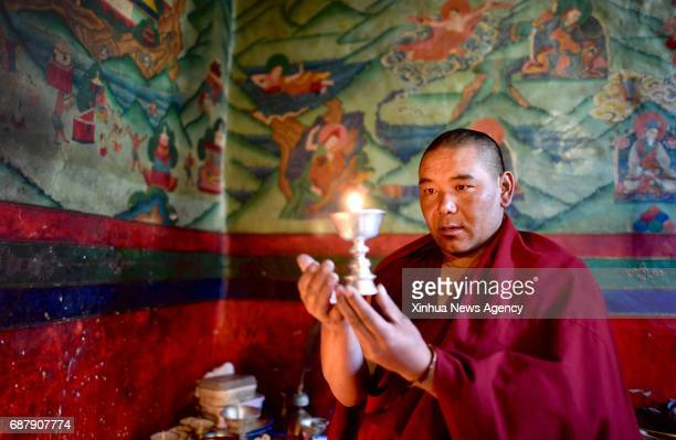 LHASA May 17 2017 Lama Ngawang Peljor lits a butter lamp at the Rongpu Monastery near Mount Qomolangma in southwest China's Tibet Autonomous Region...