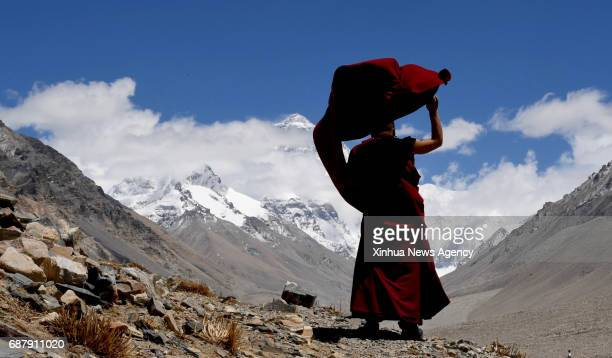 LHASA May 17 2017 Lama Ngawang Peljor looks at Mount Qomolangma at the Rongpu Monastery in southwest China's Tibet Autonomous Region May 17 2017...
