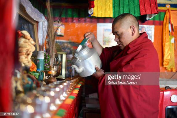LHASA May 17 2017 Lama Ngawang Peljor pours water into cups in front of a niche in his dormitory at the Rongpu Monastery near Mount Qomolangma in...