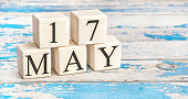 May 17th. Wooden cubes with date of 17 May on old blue wooden background.