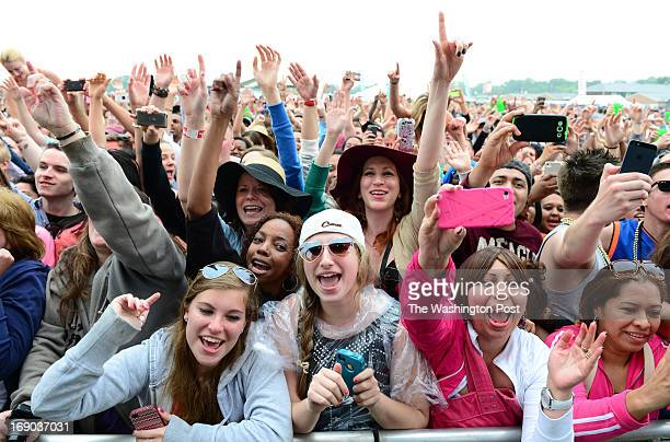 Fans scream and jump as musician Pitbull performs in the infield during the 138th running of the Preakness Stakes on May 18 2013 in Baltimore MD