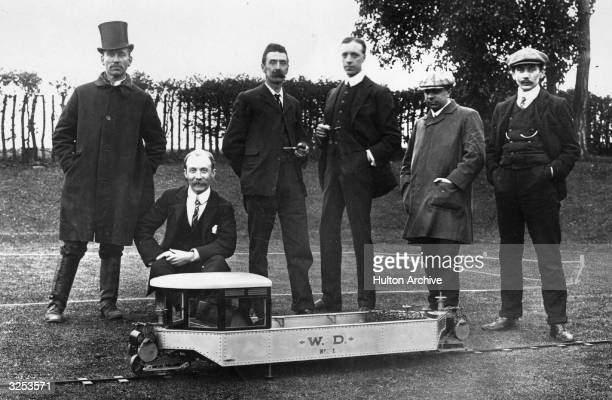 Louis Brennan and his assistants pose with a model of his invention the Brennan Monorail