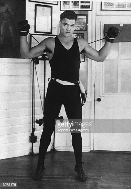 Jack Dempsey the heavyweight boxing champion nicknamed 'The Mauler' working out with weights
