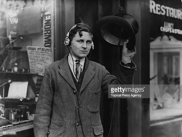 Eighteen year old inventor H Day wearing headphones attached to a wireless under his top hat