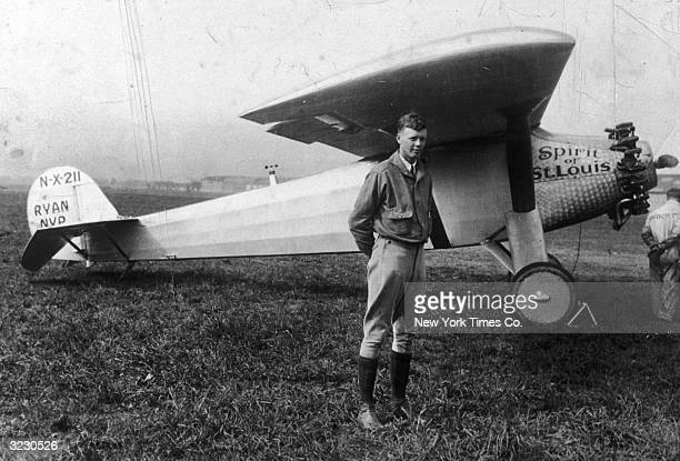 Fulllength portrait of American aviator Charles Augustus Lindbergh posing under the wing of his Ryan monoplane Spirit of St Louis on the grass of an...