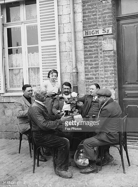 A waitress smokes a cigarette as she pours wine for clients enjoying a drink outside the Eloi Cafe near Mount Street London