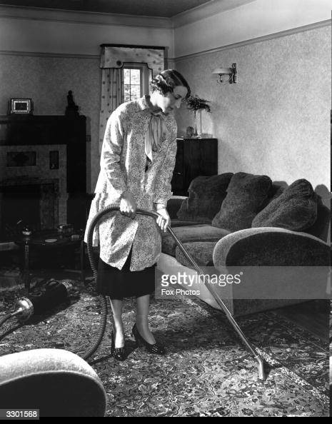 A housewife using a vacuum cleaner in the living room