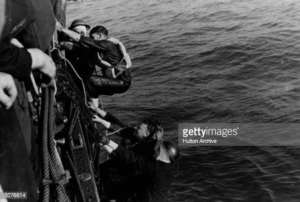 A British ship rescues soldiers from a landing craft sunk during an operation