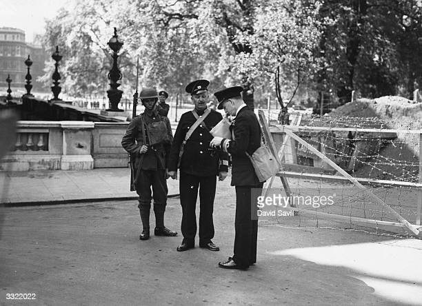 A policeman and an armed guard check passes at a barbedwire checkpoint at the Admiralty London