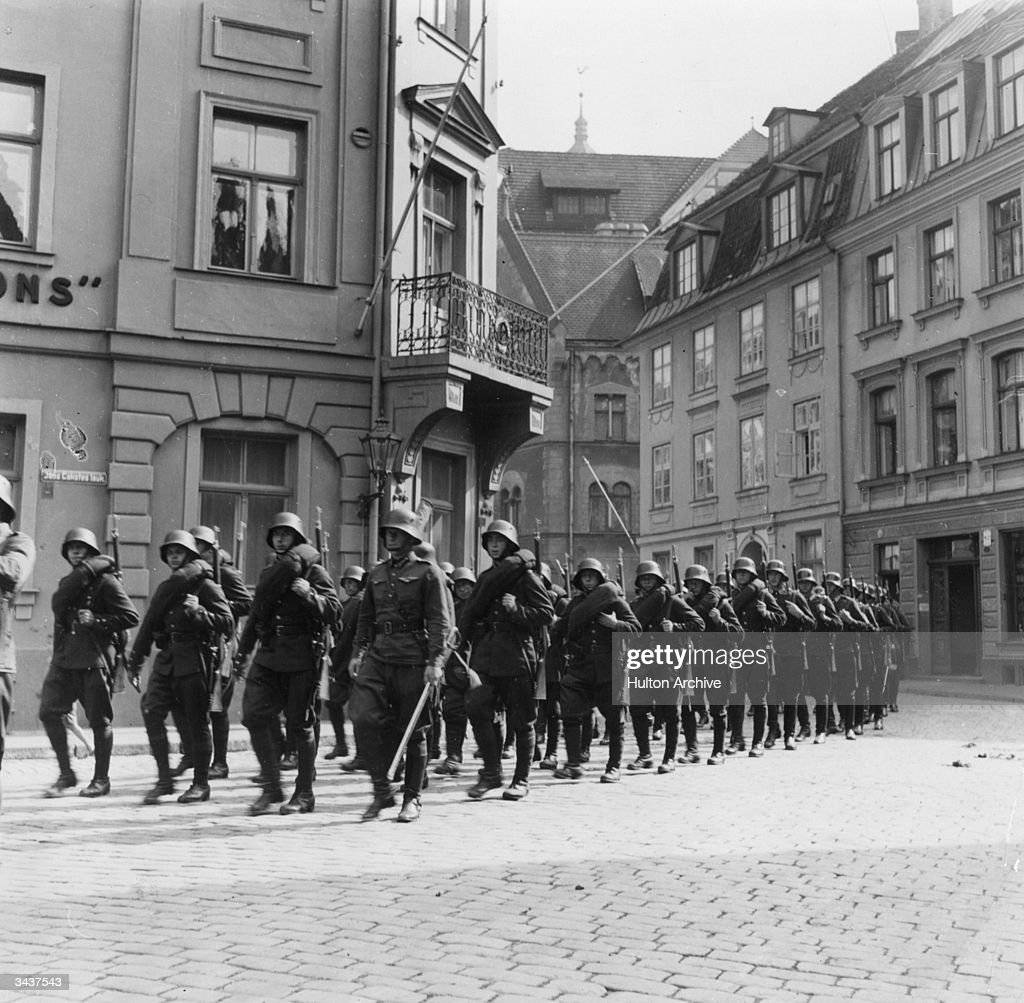 German soldiers marching through a town in Holland during WW II