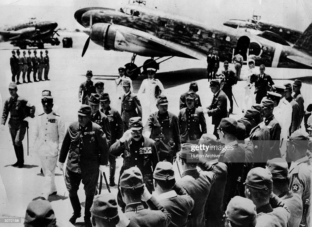 Premier Tojo arriving in Manila. He responds to the salute from General Waui Ehk of the Japanese Administration and the Commander of the Imperial Japanese Fleet (in the white uniform).