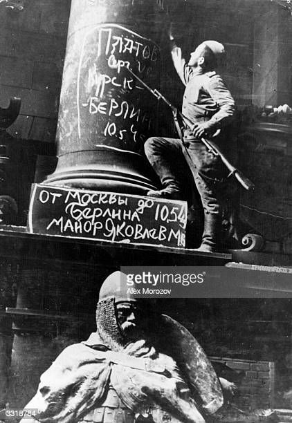 A Soviet soldier putting his signature on a column of the Reichstag Germany The words over the statue show that a Major Iakovlev fought all his way...
