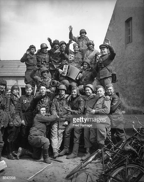 American and Soviet troops enjoying a sing song on a Russian tank after the link up near Griebo in Germany
