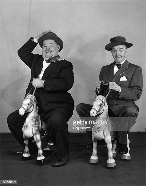 Comedian and actor Oliver Hardy and his partner Stan Laurel on a pair of wooden horses