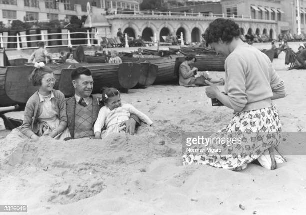 A fully clothed man and his two daughters pose buried in sand whilst his wife takes a photograph of them
