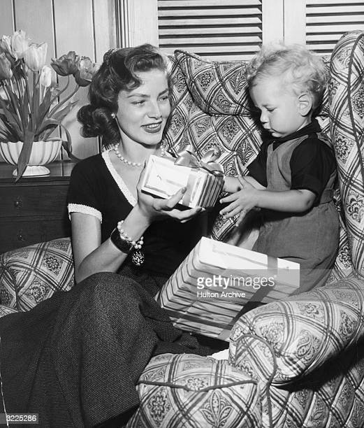 American actor Lauren Bacall sits in an armchair and smiles as her infant son Stephen Bogart presents her with two wrapped gifts for Mother's Day