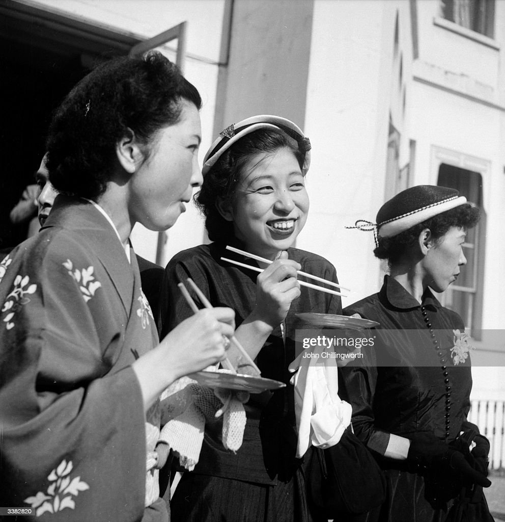 Japanese women eating sushi whilst they wauit to catch a glimpse of Prince Akihito, in England as a coronation guest of the Queen. Original Publication: Picture Post - 6521 - Give This Boy A Break - pub. 1953