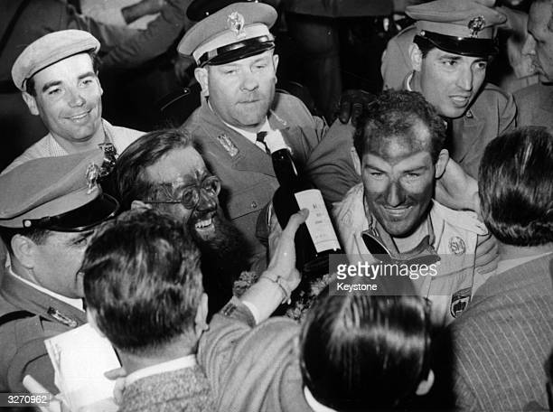 English motor racing driver Stirling Moss and his codriver Jenkinson surrounded by Italian police after they won the Italian Mille Miglia