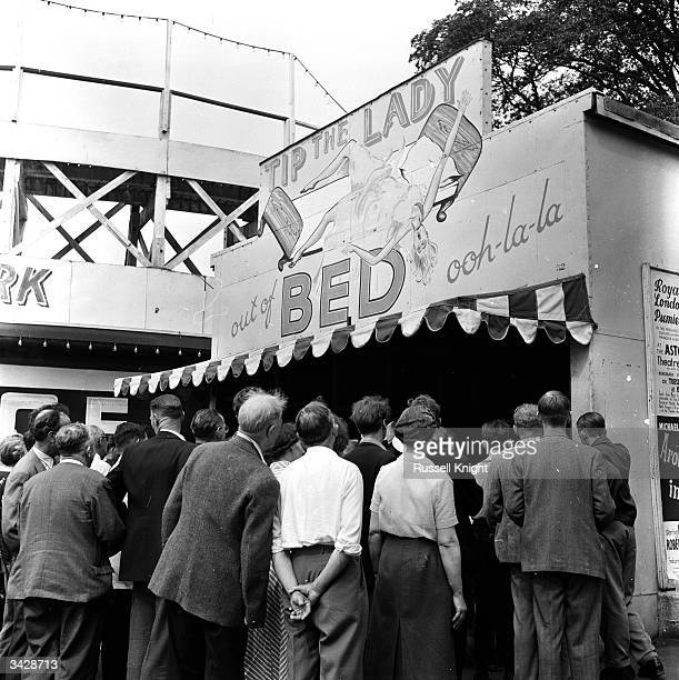 Visitors gather at the 'Tip the Lady out of the Bed' stall at London's Festival Pleasure Gardens in Battersea