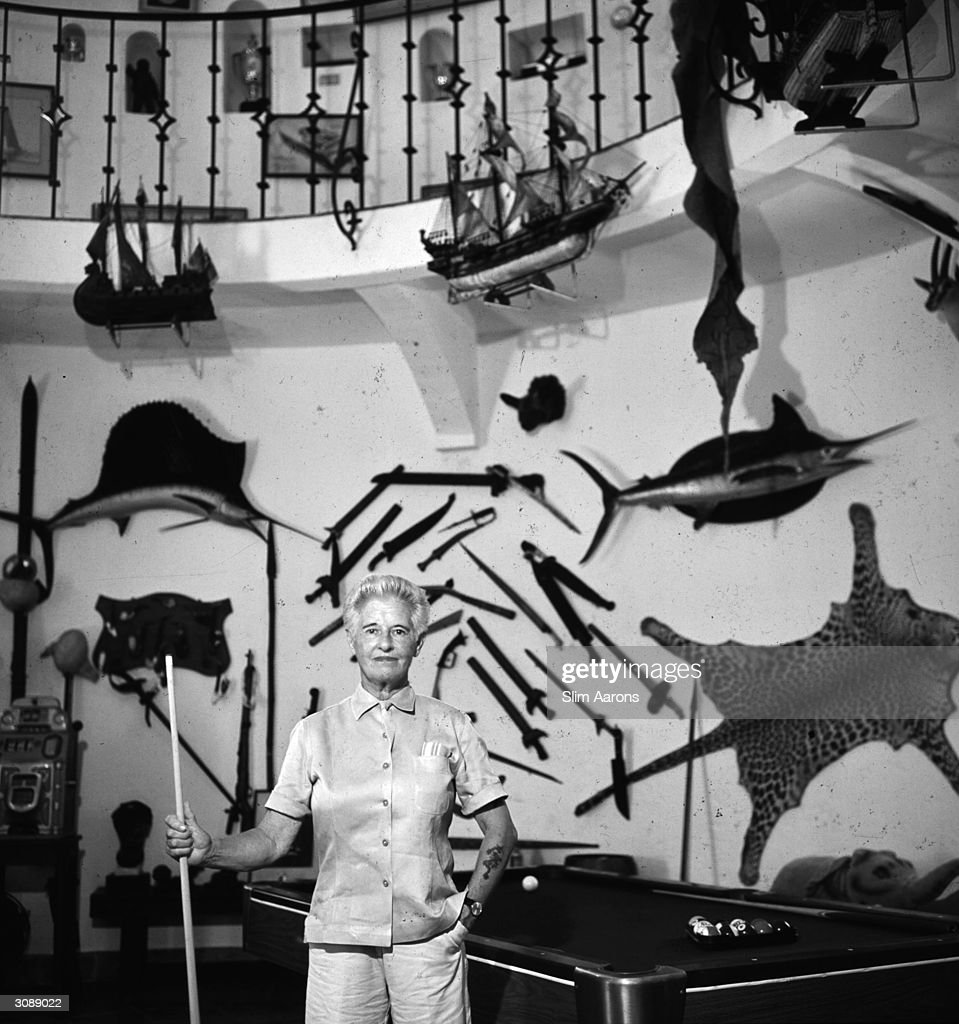 Marion B Carstairs stands amidst her trophies stuffed fish leopard skin and weapons plus a pool table in her museum on her private island Little...