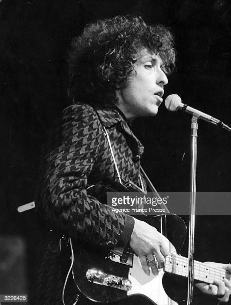 Profile view of American rock and folk musician Bob Dylan singing into a microphone and playing guitar during a concert at the Olympia music hall in...