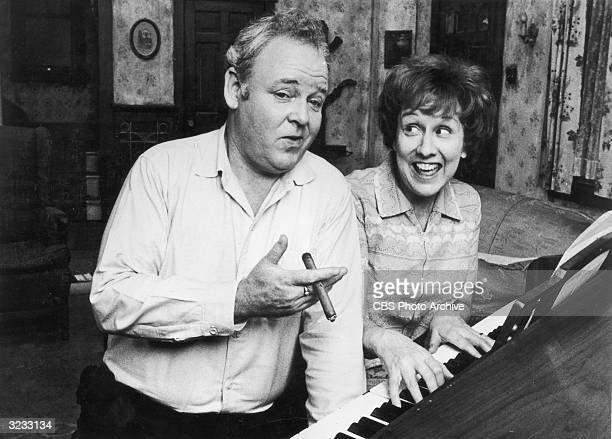 American actors Carroll O'Connor and Jean Stapleton sing as they sit at a piano in a still from the television series 'All in the Family' O'Connor...