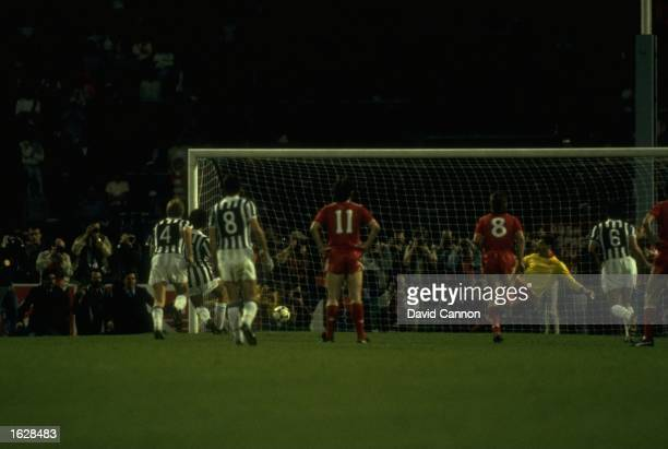 Michel Platini of Juventus scores a goal as Bruce Grobelaar of Liverpool dives the wrong way during the European Cup Final at the Heysel Stadium in...