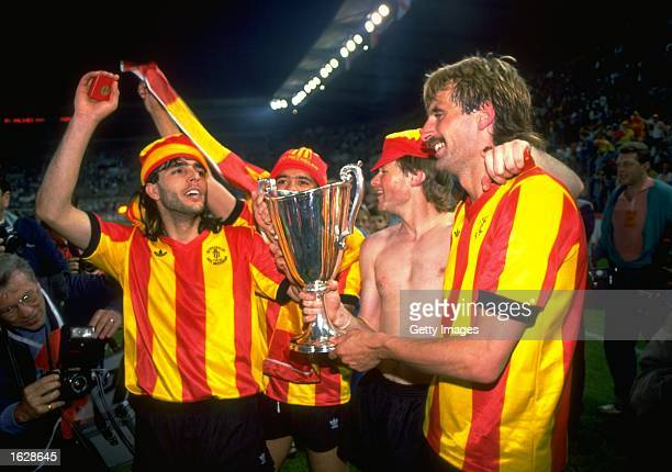 Mechelen players Ohana De Wilde Koeman and Den Boer celebrate with the trophy after their victory in the European Cup Winners Cup final against Ajax...