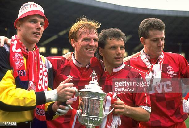 Theo Snelders McLeish Gillhaus and Brian Irvine all of Aberdeen celebrate with the trophy after their victory in the Scottish Cup Final against...