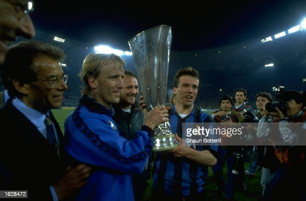 Andreas Brehme and Lothar Matthaus of Inter Milan hold the trophy after their victory in the UEFA Cup Final against Rome at the Olympic Stadium in...