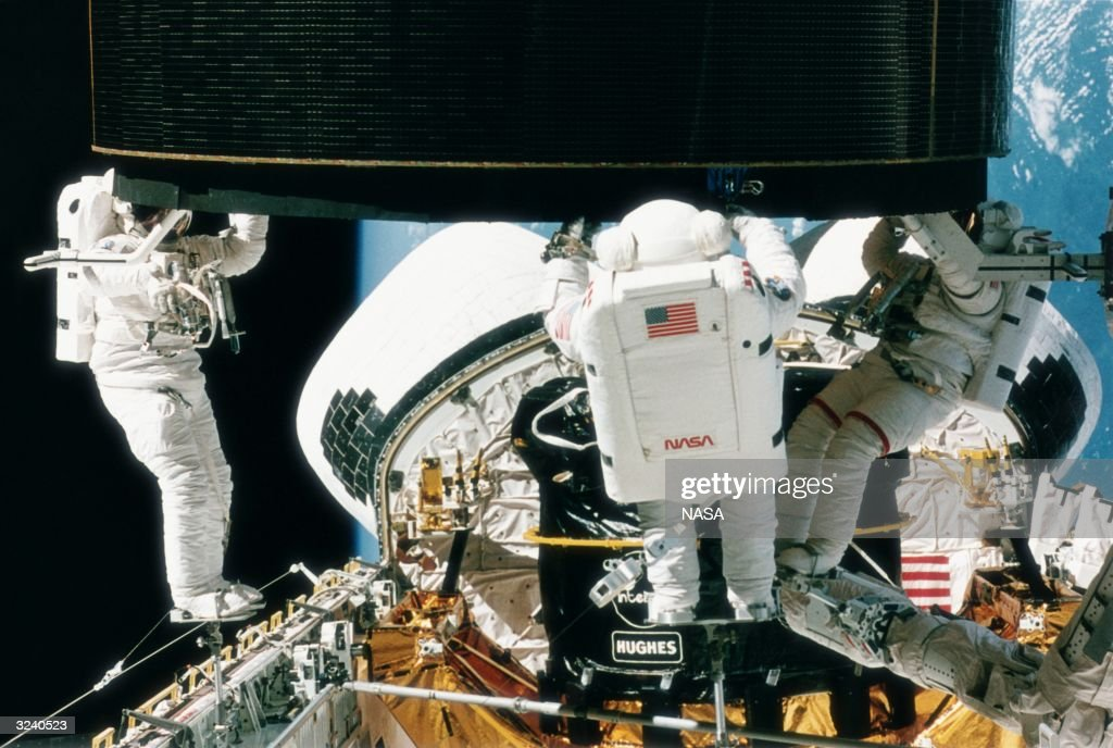 Richard Hieb, Thomas Akers and Pierre Thuot (left to right) fitting a new motor to the stranded Intelsat VI F3 communications satellite during a spacewalk that lasted a record breaking 8 hours and 29 minutes.