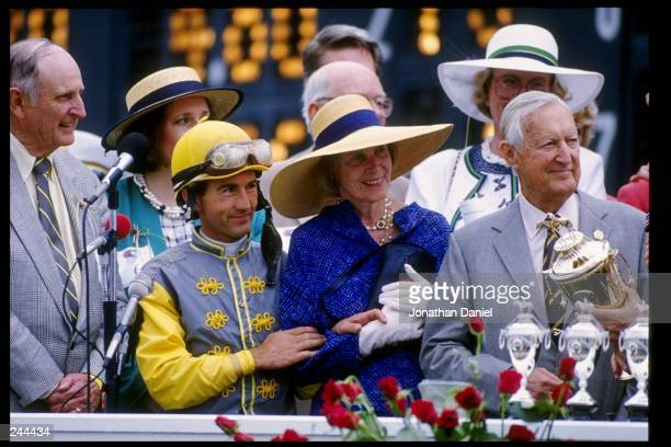 Trainer Mack Miller stands with jockey Jerry Bailey and watches as owner Paul Mellon accepts the winner''s trophy for the Kentucky Derby at Churchill...