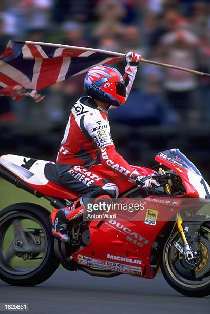 Carl Fogarty of Great Britain on the Ducati 916 waves the Union flag to his home fans during round three of the World Championships at Donington Park...