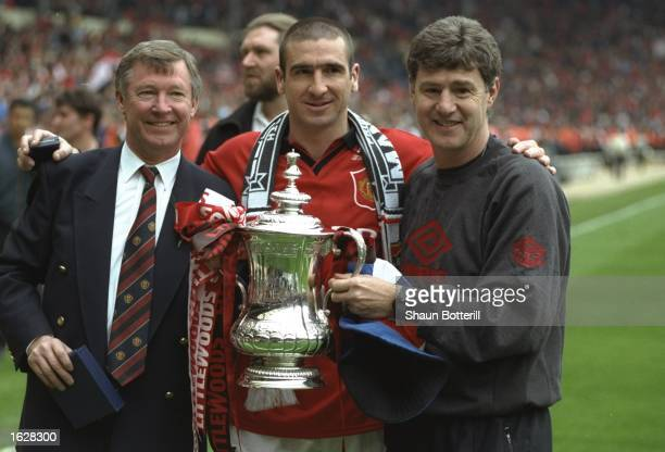 Alex Ferguson Manager of Manchester United Eric Cantona and Brian Kidd both of Manchester United hold the trophy after winning the F A Cup Final...