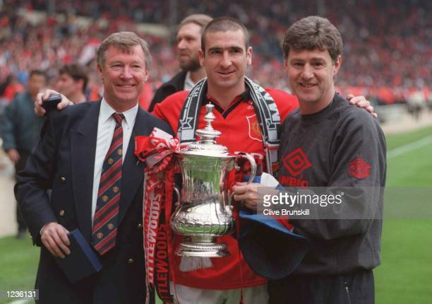 Eric Cantona Alex Ferguson and Bryan Kidd with the trophy after Man Utd's victory over Liverpool in the 1996 FA Cup Final between Manchester United v...