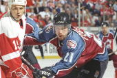 Center Peter Forsberg of the Colorado Avalanche checks center Steve Yzerman of the Detroit Red Wings during a playoff game at the Joe Louis Arena in...