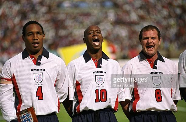 Captain Paul Ince of England and Liverpool sings the National Anthem with fellow teammates Ian Wright and Paul Gascogne during the match between...