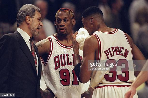 Dennis Rodman Scottie Pippen of the Chicago Bulls listen to head coach Phil Jackson during the game against the Charlotte Hornets at the United...