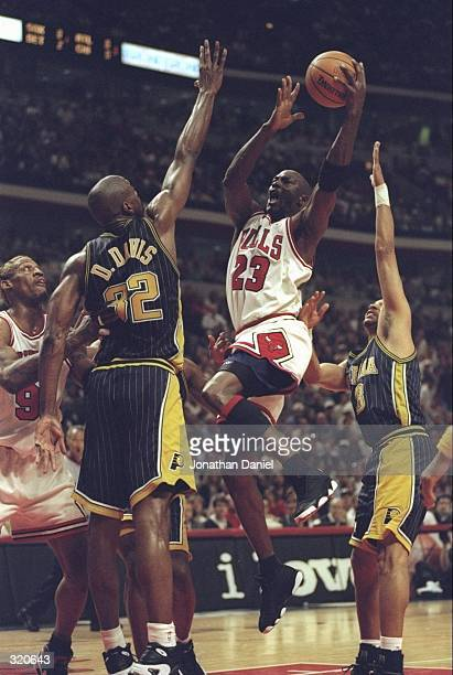Michael Jordan of the Chicago Bulls drives to the basket over Dale Davis of the Indiana Pacers during game seven of the Eastern Conference Finals at...