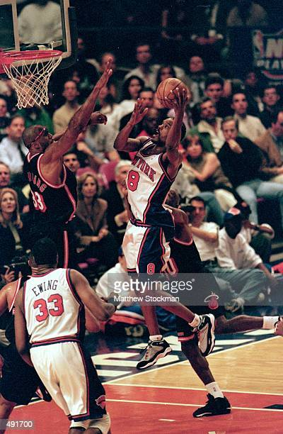 Latrell Sprewell of the New York Knicks jumps with the ball to make a basket as Alonzo Mourning of the Miami Heat reaches to block him during the NBA...