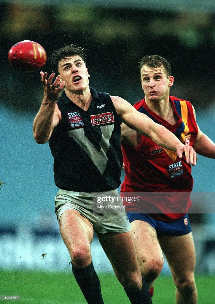 Matthew Lloyd number 18 for Victoria attempts to mark in front of Essendon team mate Sean Wellman number six for South Australia during the State of...