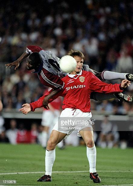 Teddy Sheringham of Manchester United is challenged by Samuel Kuffour of Bayern Munich during the European Champions League Final in the Nou Camp...