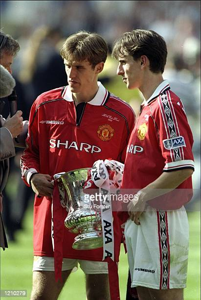 The two brothers Gary and Phil Neville of Manchester United celebrate with the trophy after the AXA FA Cup Final match against Newcastle United...
