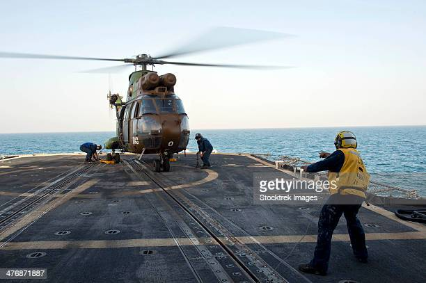 May 20, 2013 - Sailors place chocks and chains on a French army SA 380 Puma helicopter after landing on the flight deck of USS Hue City.