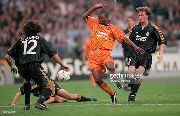 Joceyln Angloma of Valencia is surrounded by Real Madrid players during the European Champions League Final 2000 at the Stade de France SaintDenis...