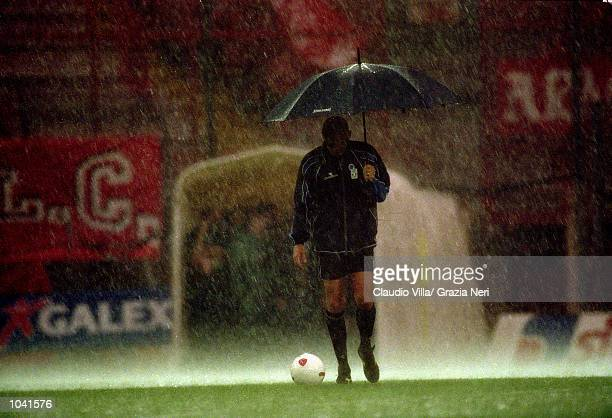 Referee Pierluigi Collina tests waterlogged pitch during the Italian Serie A match between Perugia and Juventus at the Stadio Curi A in Perugia Italy...