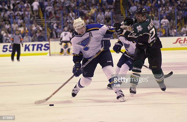 Al MacInnis of the St Louis Blues gets his jersey hooked from behind by Richard Matvichuk of the Dallas Stars as MacInnis tries to get a shot on net...