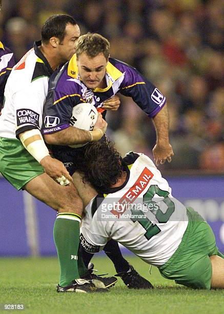 Danny Williams for the Storm is tackled by Jason Croker and Luke Davico for the Raiders during the round 13 NRL match between the Melbourne Storm and...