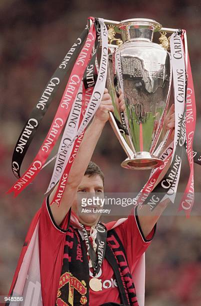 Denis Irwin of Manchester United lifts the trophy and celebrates being crowned FA Carling Premier League Champions after the match against Derby...