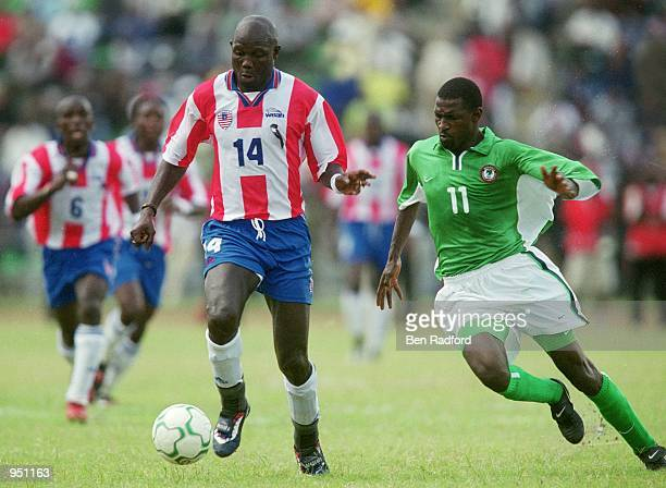 George Weah of Liberia takes the ball past Garba Lawal of Nigeria during the World Cup 2002 Group B Second Round Qualifying match played at Port...